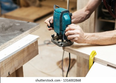Manual wood concept. Cropped close up photo hands of cabinetmaker handcraft mature man plunge tool in wood made make furniture in garage or workroom
