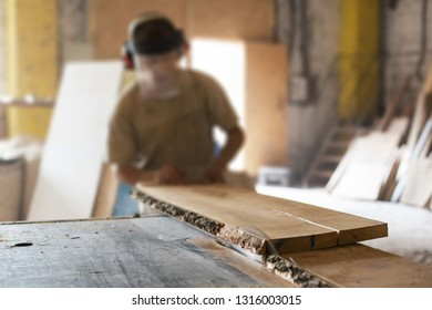 Manual wood small business concept. Cabinetmaker or unrecognizable mature handyman push wooden plank board on saw table make furniture in garage or workroom