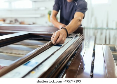 Manual worker assembling PVC doors and windows. Manufacturing jobs. Factory for aluminum and PVC windows and doors production. Selective focus.