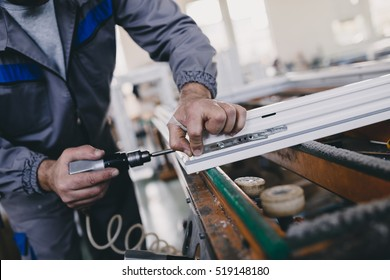 Manual worker assembling PVC doors and windows. Manufacturing jobs. Selective focus. Factory for aluminum and PVC windows and doors production.