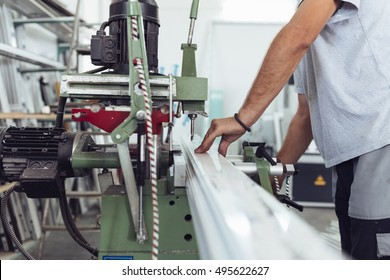 Manual worker doing his job on big machine for profile cutting. Manufacturing jobs. Selective focus. Factory for aluminum and PVC windows and doors production.