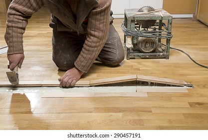 Manual worker fixing wooden floor ruined from moisture and water leak.
