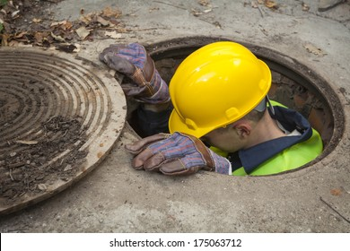 Manual worker inside manhole looking for the problem.
