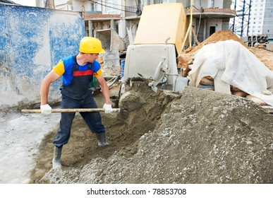 manual worker with shovel at construction works in building area