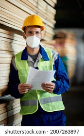 Manual worker wearing protective face mask while working at lumber warehouse and looking at camera.
