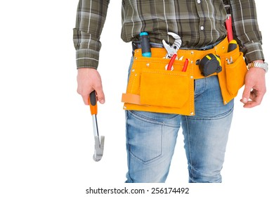 Manual worker wearing tool belt while holding hammer on white background