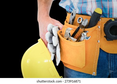 Manual worker wearing tool belt while holding gloves and helmet against black