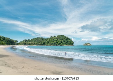 Manuel Antonio beach in Costa Rica with a woman splashing in the ocean in the distance
