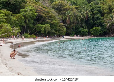 MANUEL ANTONIO BEACH, COSTA RICA - May 6, 2016: Tourists enjoying the Pacific Ocean in a secluded and protected beach at Manuel Antonio National Park in Costa Rica on May 6, 2016.