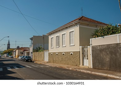 São Manuel, southeast Brazil - October 14, 2017. Working-class old house with wall in an empty street on a sunny day at São Manuel. A cute little town in the countryside of São Paulo State.