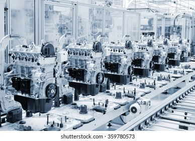 Manufactoring line with new engine parts. Photo is tone to cool blue color. Car factory. Car parts. Engine factory. New engine factory. Engines on line.