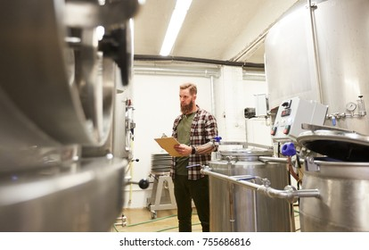 manufacture, business and people concept - man with clipboard working at craft brewery or non-alcoholic beer production plant