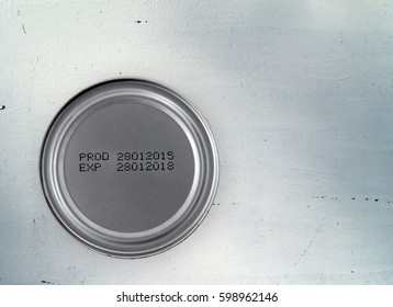 manufacture date and expiry date printed on the bottom of aluminum can on old white zinc kitchen table, information of product for consumer, top view