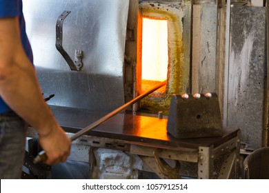 Manufacture worker heats glass in stove for heating the glass. close up shot, focus on open stove door