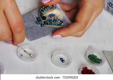 Manufacturer of brooches made of Swarovski crystals, handmade. Beads and gemstones. A woman sewing with a needle.