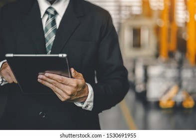 Manufacturer or businessman working on tablet while searching for technical data Industry logistic or Import and export Factory. Maintenance engineer using digital tablet control, inspect Project