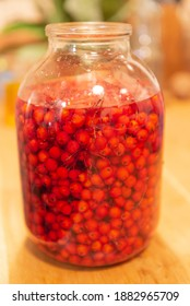Manufacturer of tincture of mountain ash. Rowan berries in a glass jar. Vodka poured red berries.