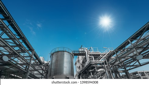Manufacturing of chemical industrial plant with pipeline and stainless tank on blue sky background