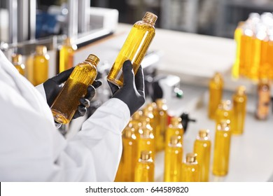 Manufacturing concept. Factory worker holding two glass bottles with yellow liquid comparing quality between them. Factory process of production shampoo. Technology, innovation and scientific concept
