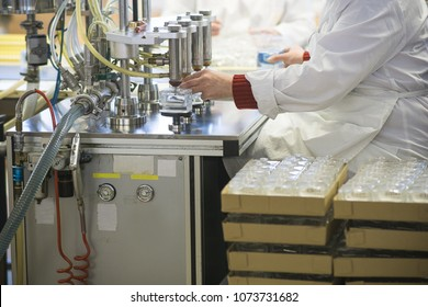 Manufacturing and filling perfume bottles in a factory. Cosmetics production conveyor line in an industrial environment. A lady in a white laboratory coat working