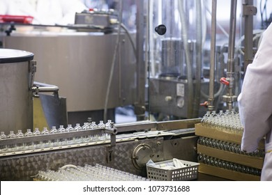 Manufacturing and filling perfume bottles in a factory. Cosmetics production conveyor line and heavy machinery in an industrial environment. White lab coats