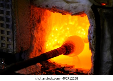 Manufacturing glass in a traditional oven, the glassblower working on a handmade vase of melted glass on a rod, selected focus and narrow depth of field