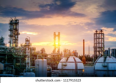 Manufacturing of oil and gas refinery industrial or Petrochemical industry plant on sunset sky background with smoke stacks and gas sphere tanks