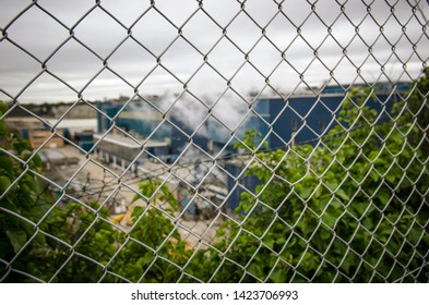Manufacturing plant seen through perimeter fence.