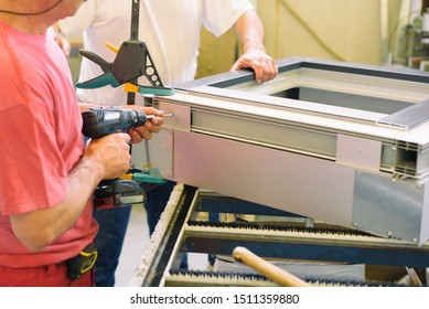 A manufacturing worker assembles a pvc window. Factory for aluminum and PVC windows and doors production
