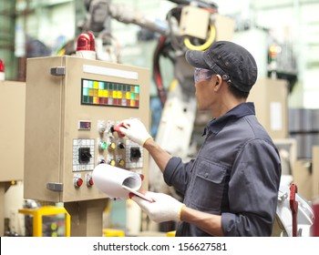 Manufacturing worker operating a robot machine with a control panel