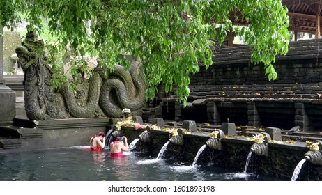 MANUKAYA, INDONESIA- MARCH,22, 2018: wide view of two women and an elephant statue at holy spring fountain, bali
