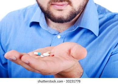 Manwith blue shirt holding pills on his hand