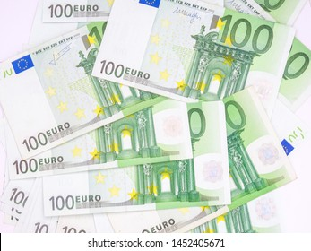 Many 100 euro bills spread on white background