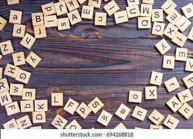 Many abc education cube scattered on wooden table.