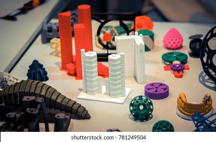 Many abstract models bright colorful objects printed on a 3d printer on a white table. Fused deposition modeling, FDM. Progressive modern additive technology. Concept of 4.0 industrial revolution