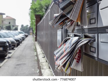 Many advertising leaflets are hanging from an overloaded letterbox