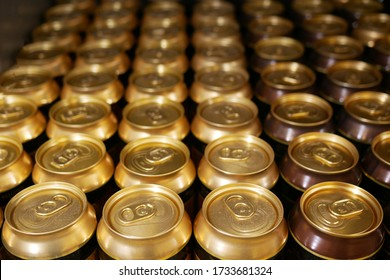Many aluminum cans stand in a row on a shelf close-up. Tops of aluminum cans closeup in a row on a rack.