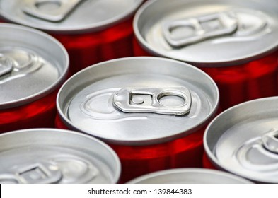 Many aluminum red cans of soft drink cola close-up