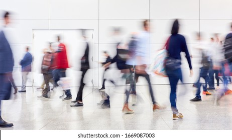 Many anonymous blurred people go on trade fair or in mall