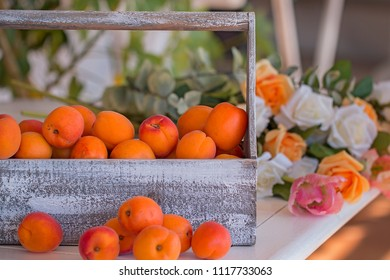 Many apricots in a wooden basket. Background: flowers.