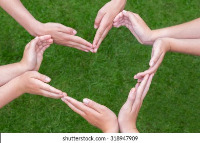 Many arms and hands of girls make heart shape above green grass