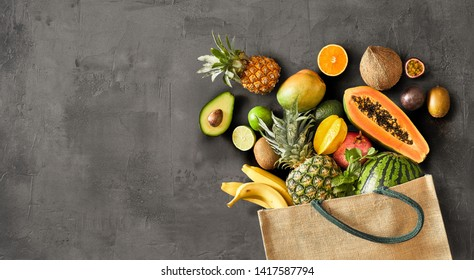 Many assorted fruits falling out of canvas bag that fell over on top of dark grey background surface