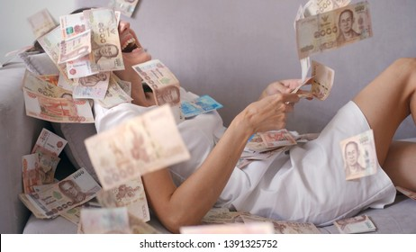 Many banknotes fly in the air overhead in slow motion. A girl lies and a lot of money falls on her. happy woman rejoices huge wealth of money.