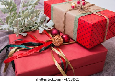 Many beautiful luxury Christmas gifts on a brown carpet at home. Red paper boxes with decor, gifts for Christmas and New Year. Celebrating Christmas