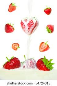 many beautiful strawberries falling in milk