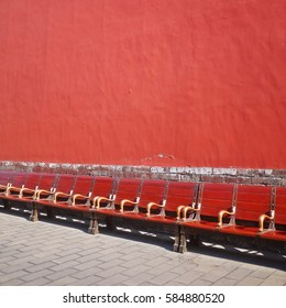 Many benches on the sidewalk with red exterior wall background at Forbidden City in Beijing, China.