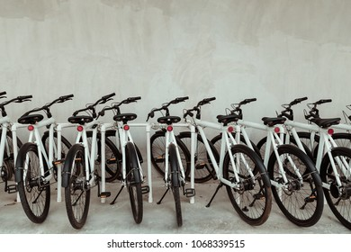 Many bicycle in a row. White Bicycles stand on a parking for rent. Eco friendly transportation concept.