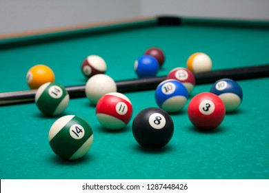 Many billard balls and a cue in a leisure club environment, lots of billiards on the table, wallpaper background