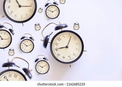 Many black alarm clock on white background. Flatlay topview