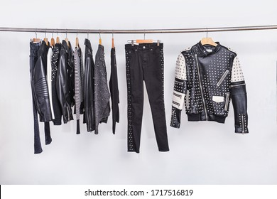 Many black different clothing , pants,sweater,set of on the racks